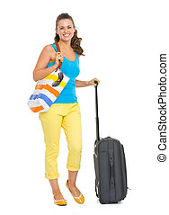 Full length portrait of happy young tourist woman with wheel bag