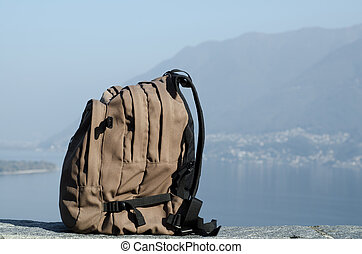 Backpack and mountains over an alpine lake