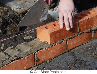 Bricklayer - Construction worker laying bricks showing...