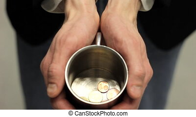 Begging Businessman - Business man extending metallic cup...