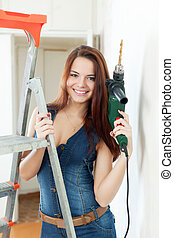 woman in dungarees with drill near stepladder in interior