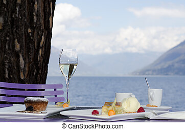 Table with dessert and champagne and coffe with seascape and...