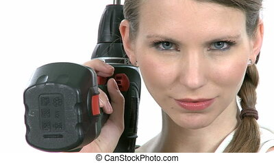 Young craftswoman with a power drill in front of white...