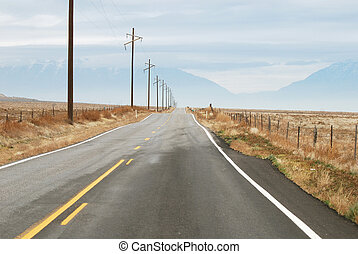 Two lane highway with row of telephone poles and wires.