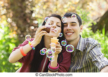 Couple Relaxing in the Park with bubble blower Spring time