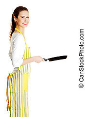 Teen girl dressed in apronwith frying pan - Young smiling...
