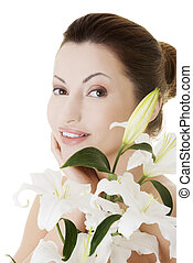 Woman with health skin and with lily flower