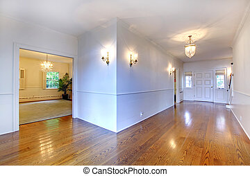 Large bright hallway with hardwood floor and dining room.