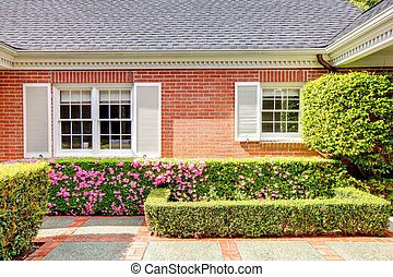 Brick red house with English garden and white window...