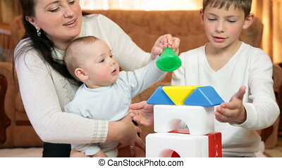 Mother and sons playing with colored blocks