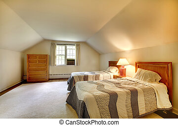 Attic bedroom with simple furniture and vaulted ceiling.