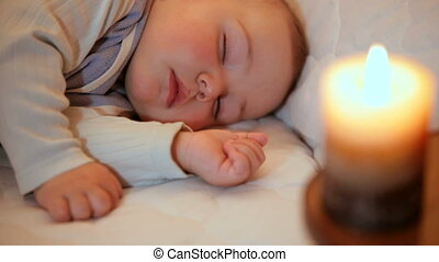 Sleeping baby in the light of burning candle. Focus on baby