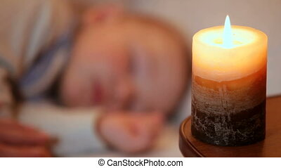 Sleeping baby in the light of burning candle. Focus on...