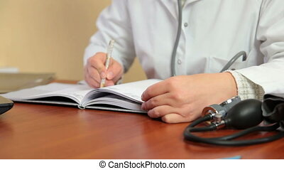 Busy female doctor writing - Busy female doctor writing at...