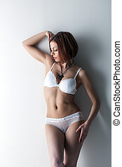 Attractive slim girl posing in white lingerie, close-up