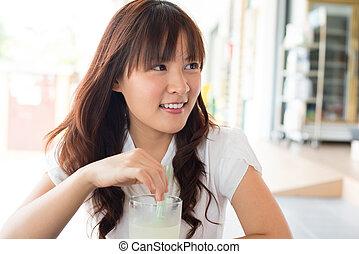 Young Asian woman enjoying drinks