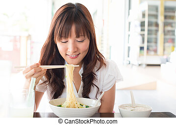 Eating noodles at restaurant Young Asian girl eating ramen...