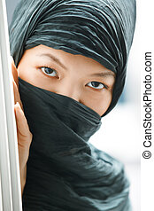 Hiding - Oriental lady in black hijab hiding