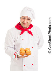 chef holding plate with 4 muffins wearing red and white...