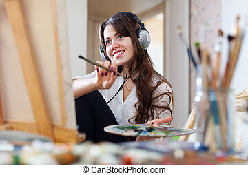 Long-haired artist in headphones paints picture -...