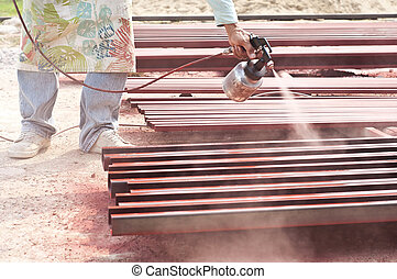 Worker painting steel bars.