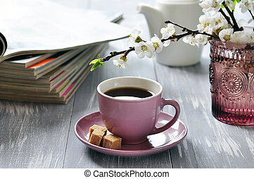 Cup of coffee with branches of blooming cherry on wooden...