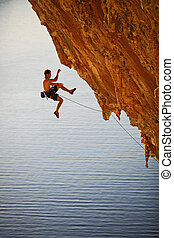 Rock climber falling of a cliff while lead climbing