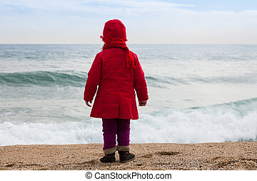 girl on beach in windy day - Baby girl on sand beach in...