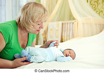 Pretty middle-aged woman holding her newborn grandson