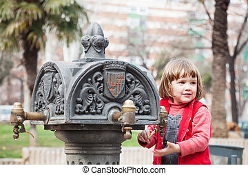 Girl using stand-pipe on street of Barcelona, Spain