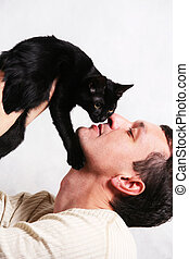 Portrait with a cat - Man covers a kitten on a white...