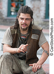 Rebel with dreadlocks and tattoos sitting outside