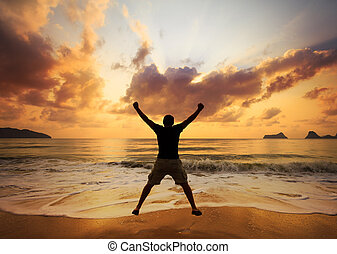 Happy man jumping over sea Sand beach at dawn