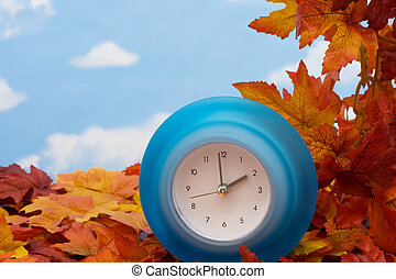 Fall Back Time Change - Fall leaves with blue clock on sky...