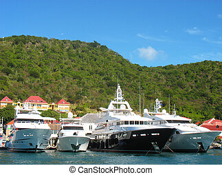 Mega yachts in Gustavia Harbor at St. Barths. The island is...