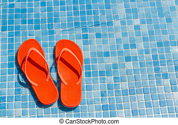 Flip flops - Orange flip flops in the swimming pool.