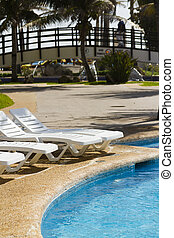 Pool chairs - white plastic pool chairs at the swimming pool...