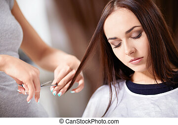 In a beauty salon - Young girl trimmed hair in a beauty...