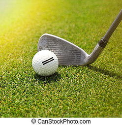 Golf player hitting the ball into the whole. Close up