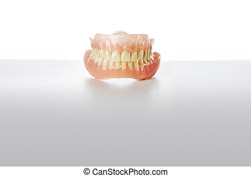 Old Dentures - Old dirty dentures on grey background.