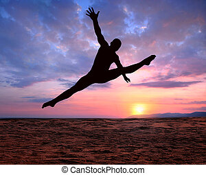 silhouette at sunset - A silhouette of a jumping man on a...