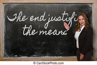 Teacher showing The end justifies the means on blackboard -...