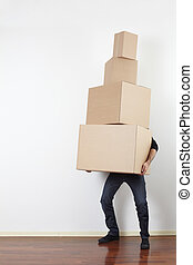 Man lifting cardboard boxes in apartment