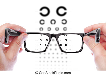 Glasses in the hands of men. Checking vision the table...