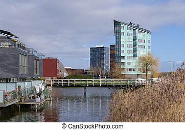 modern apartments and houses along a canal in Almere,...