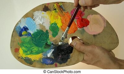 palette - traditional artist's palette , mixing black and...