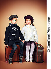 side by side - Cute little boy and girl are sitting on their...