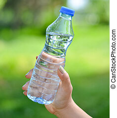 Woman hand holding water bottle against green background