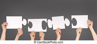 hands holding pieces of a puzzle with copy space - hands...