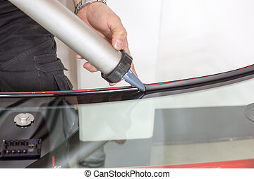 Glazier applying rubber sealing to windscreen - Glazier...